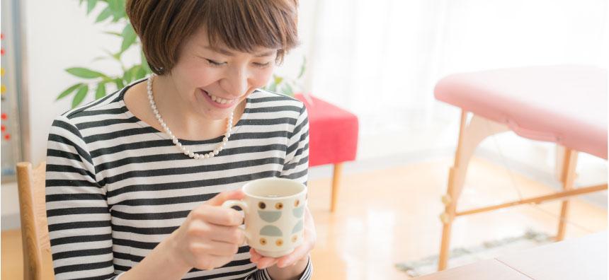 横浜キネシオロジーセラピーサロンで笑顔でお茶を飲む女性